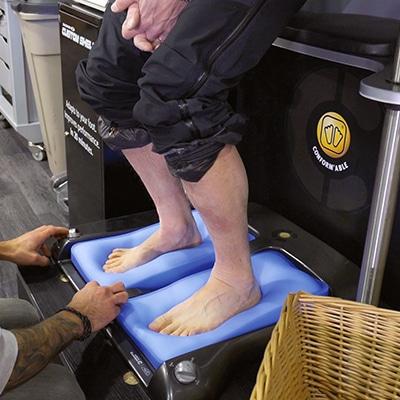Personne en appui sur des coussins pour la réalisation de moulage à la forme des pieds