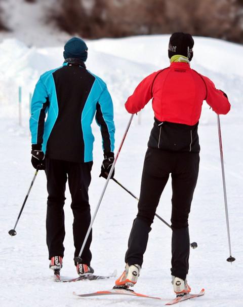 skieurs utilisant leurs skis de fond pour descendre une piste
